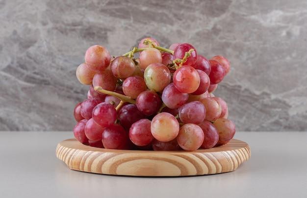 Грозди красного винограда на деревянном блюде на мраморе
