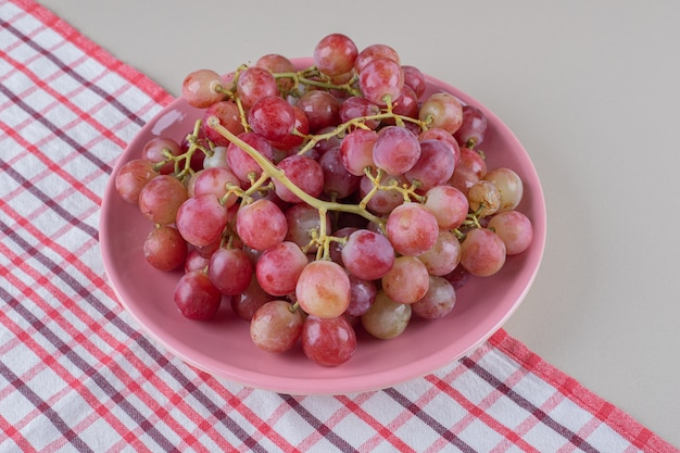 Red grape clusters on a pink platter on a towel, on marble