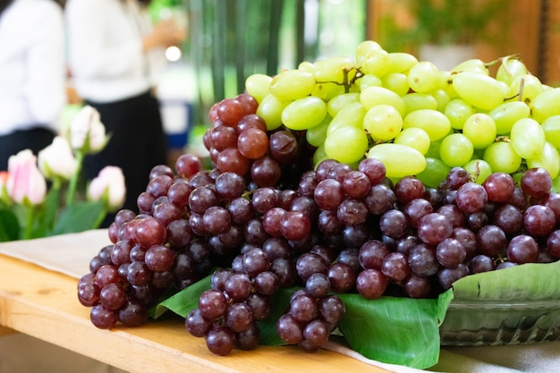 屋外の庭のフィールドの木製のテーブルに立っているステップガラスプレート上の赤ブドウは、ボケ味をぼかします。