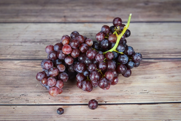 Red grape on wooden table bunch of grapes juicy fruit