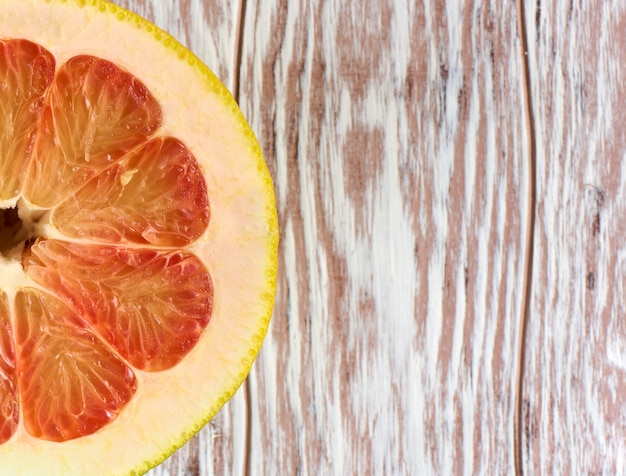Red grapefruit half on a wooden background with copy space