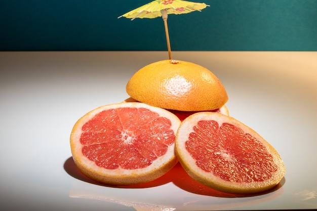 Красный грейпфрут на белом и темно-синем фоне с коктейльным зонтиком.