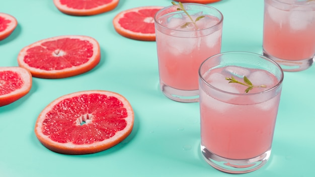 Red grapefruit slices and cocktail juice on mint background