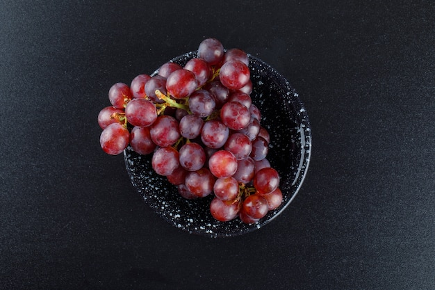 Red grapes in a bowl on dark grey,