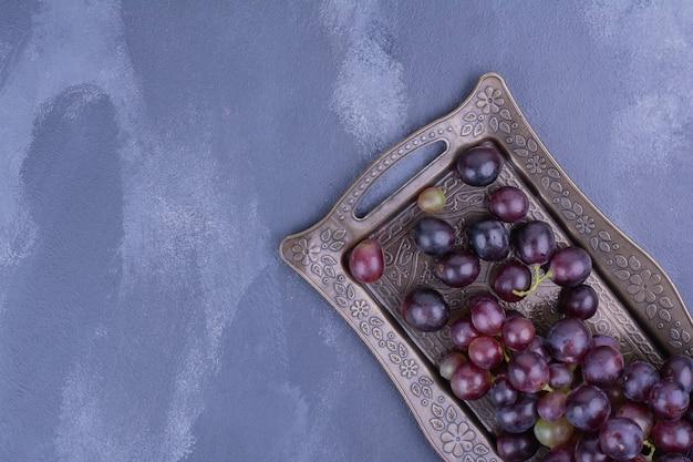 青い表面の金属製のトレイに赤ブドウ