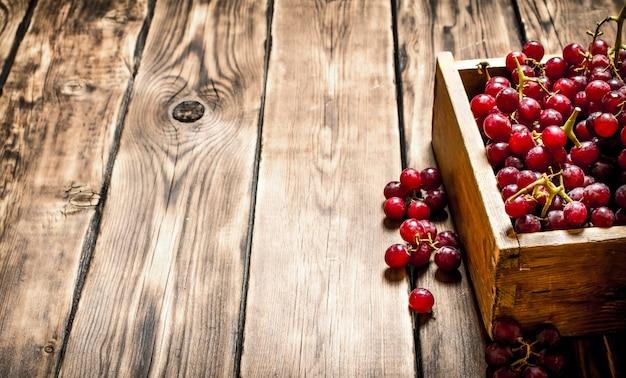 오래 된 상자에 붉은 포도. 나무 배경.