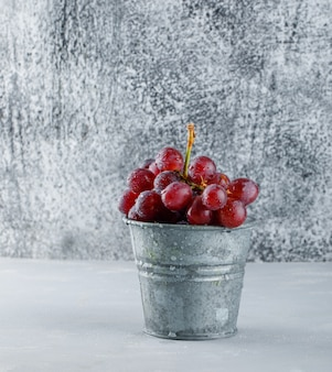 Red grapes in a mini bucket on plaster and grungy.