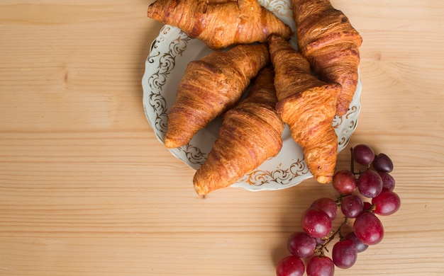 Red grapes near the baked croissant on plate over wooden background