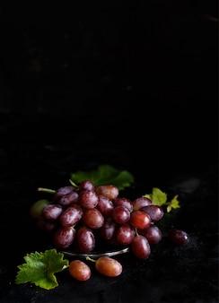 暗い背景の上の銀のボウルに赤ブドウ