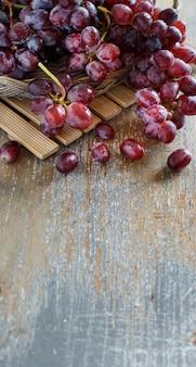 古い木製のテーブルの上の赤ブドウがクローズアップ