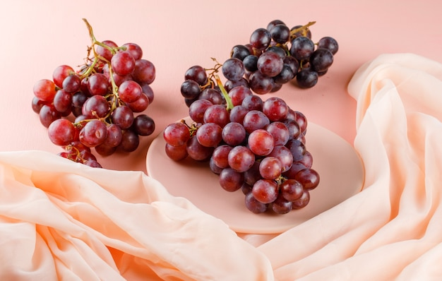 Red grapes in a plate on pink and textile. high angle view.