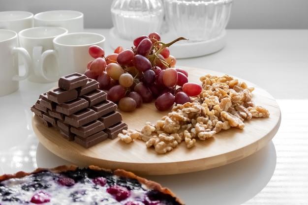 Красный виноград, грецкие орехи, шоколад и пирог лежат на белом столе