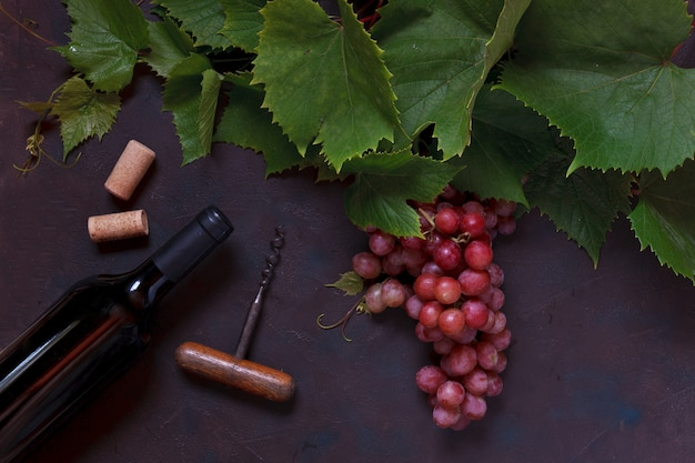 Red grapes with leaves, corks, corkscrew and bottle of red wine.