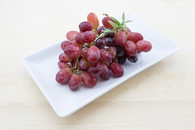 Red grapes with white plate on wooden table.