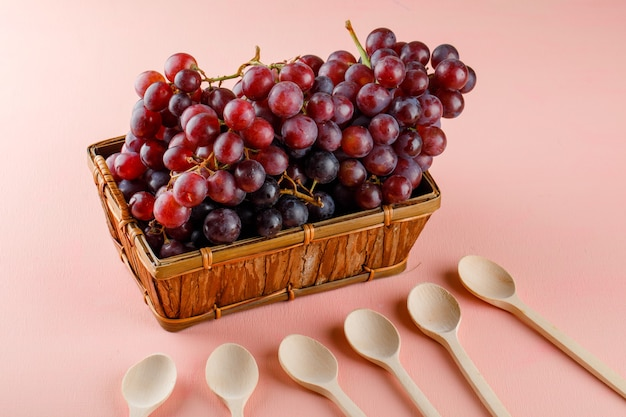 Red grapes with wooden spoons in a basket on pink, high angle view.