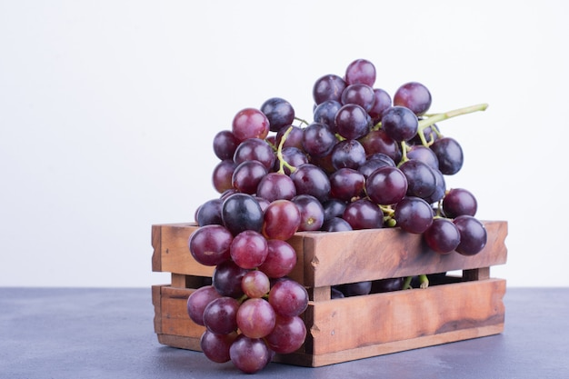 Red grapes in a wooden tray on blue surface