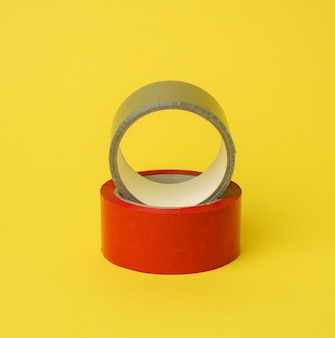 Red and gray scotch tape isolated on a yellow background, close up