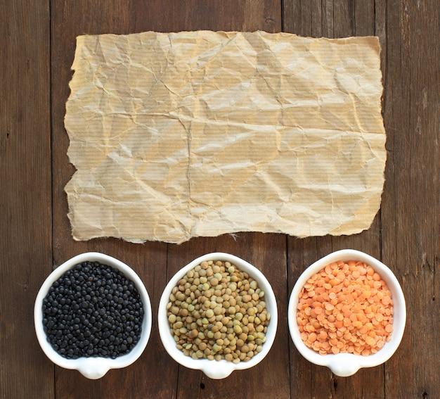 木製のテーブルトップビューにクラフトペーパーをボウルで赤、緑、黒のレンズ豆
