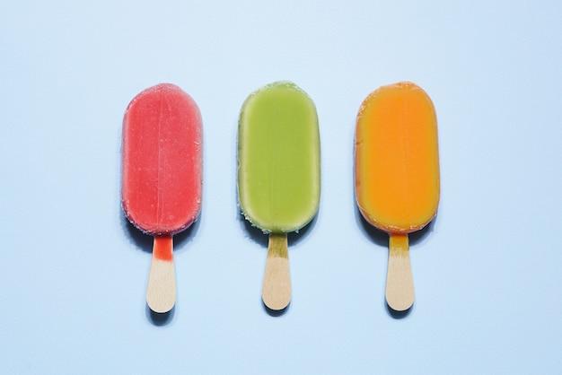 水色の背景にスティックに赤、緑、オレンジ色の冷凍ビーガンシャーベットアイスクリーム