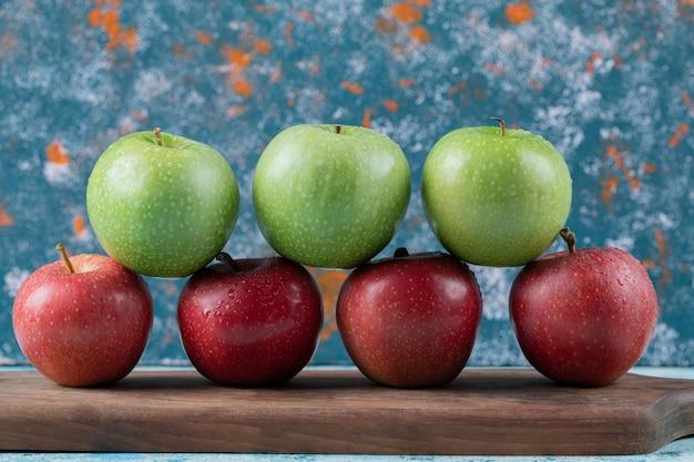 Mele rosse e verdi isolate sulla tavola di legno.