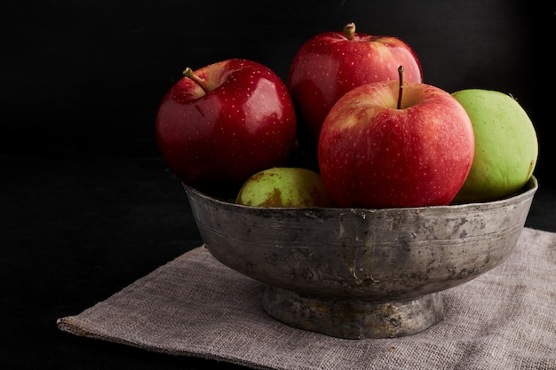 Red and green apples in a metallic bowl.