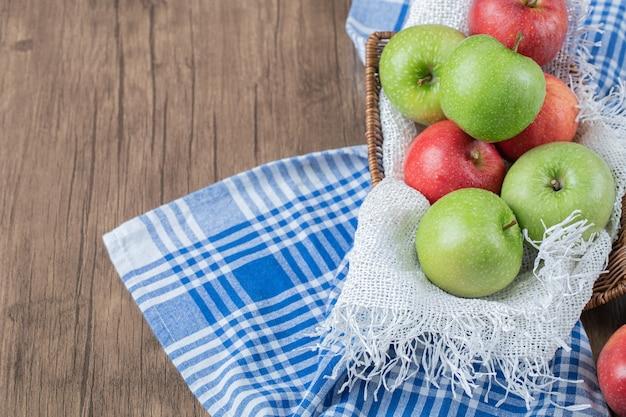 かごの中の白いタオルの上に赤、緑のリンゴ