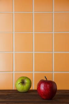 Vista laterale delle mele rosse e verdi su uno spazio di legno ed arancio del fondo delle mattonelle per testo