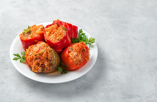 Red and green bell peppers stuffed with turkey rice and vegetables on a white plate with fresh herbs