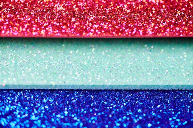 Red green blue glitter texture. new year or christmas background for greeting card. valentines day celebration. shiny sparkle design for festive decoration: wedding, holiday or anniversary party.