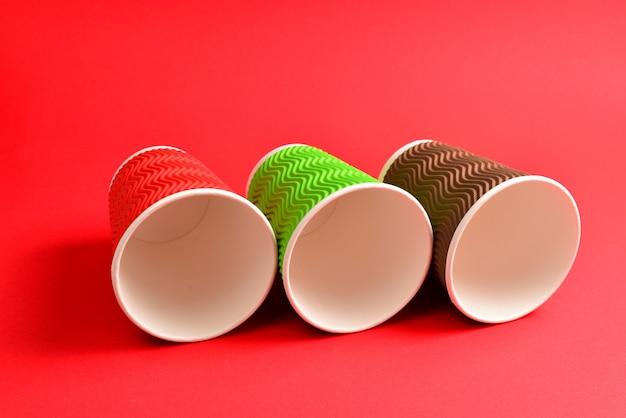 赤の背景に赤、緑、茶色の紙コップ。スペースをコピーします。
