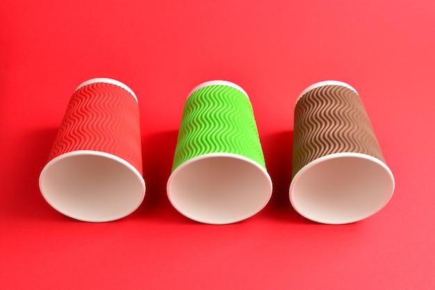 Красные, зеленые, коричневые бумажные стаканчики на красном фоне. скопируйте пространство.