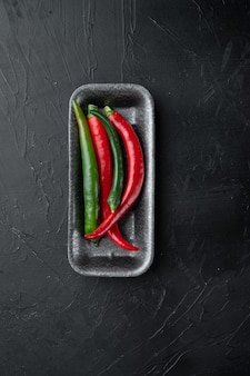 Red and green chili pepper set, in plastic tray, on black