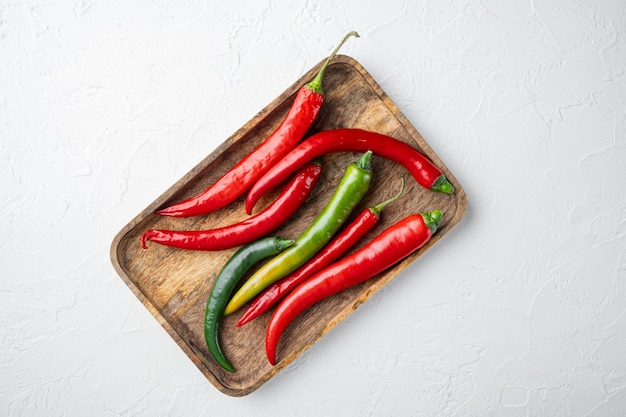 Red and green chili pepper set, on wooden tray, on white