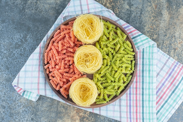 Red and green fusilli pastas with thin spaghetti in the bowl on towel, on the marble background.
