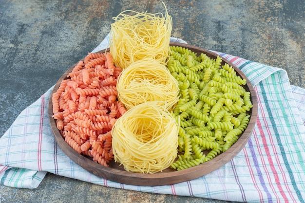 Fusilli rossi e verdi con spaghetti sottili nella ciotola su un asciugamano, sulla superficie di marmo.