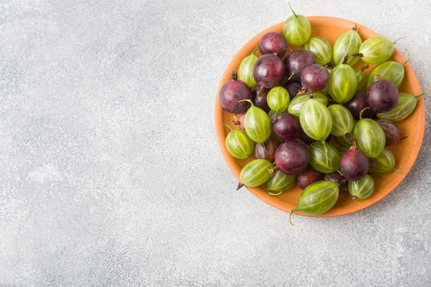 Red and green gooseberry berries in a plate on a grey surface