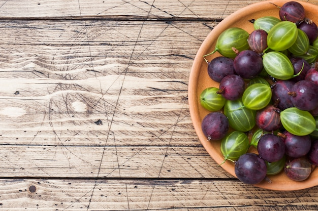 Red and green gooseberry berries in a plate on a wooden surface