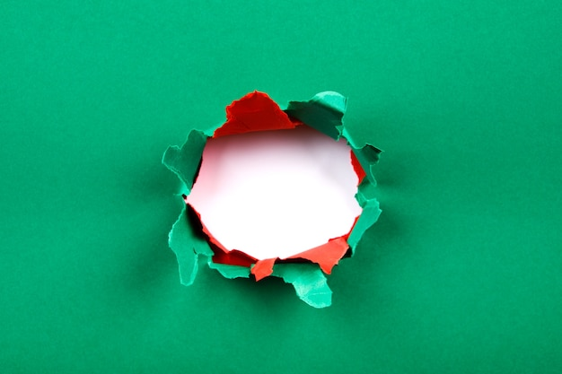 Red and green hole in the paper with torn sides