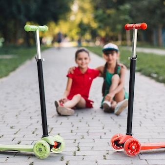 Red and green kick scooters in front of two girls sitting together on walkway