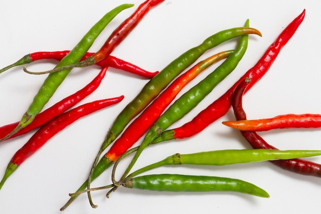 Red and green peppers on plain background