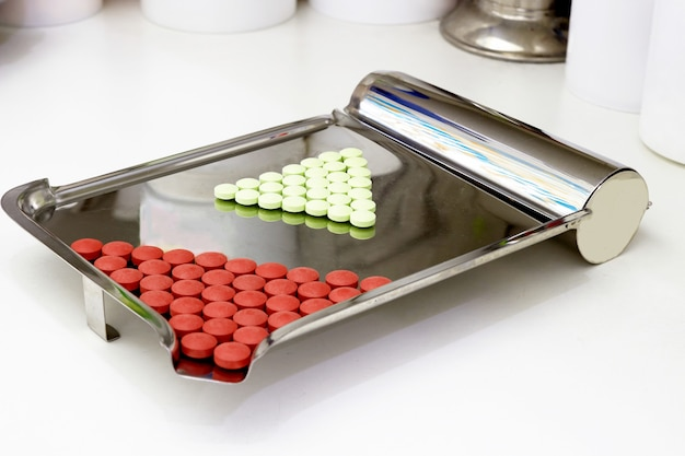 Red and green pills on counting tray on pharmacy counter