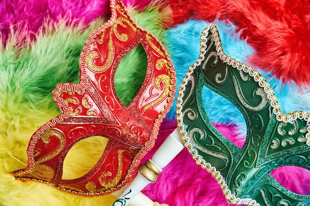 Red and green venetian mask, carnival mask on colorful background