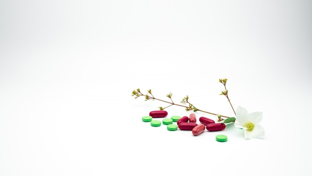 Red, green vitamin and supplement tablet and capsule pills with flower and branch on white background with copy space.