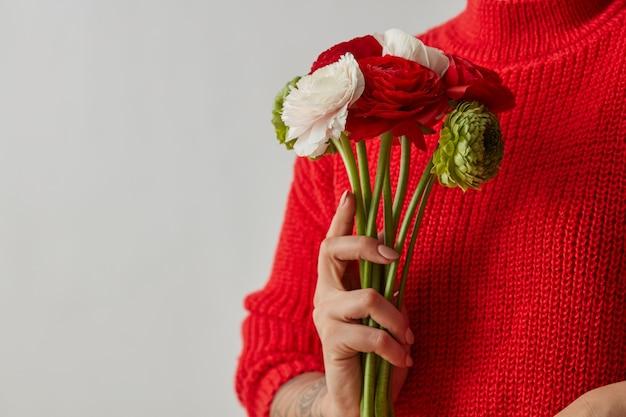 라넌큘러스의 빨강, 녹색, 흰색 꽃. 회색 배경에 복사 공간이 있는 부드러운 꽃다발을 손에 들고 있는 소녀. 어머니의 날