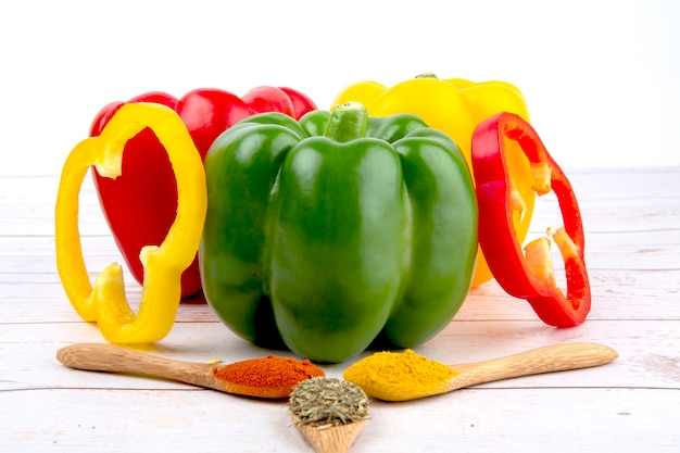 Red green yellow peppers whole and sliced and three wooden spoons with spices on wooden table