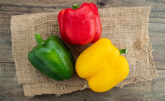 Red, green and yellow sweet bell peppers on wooden background