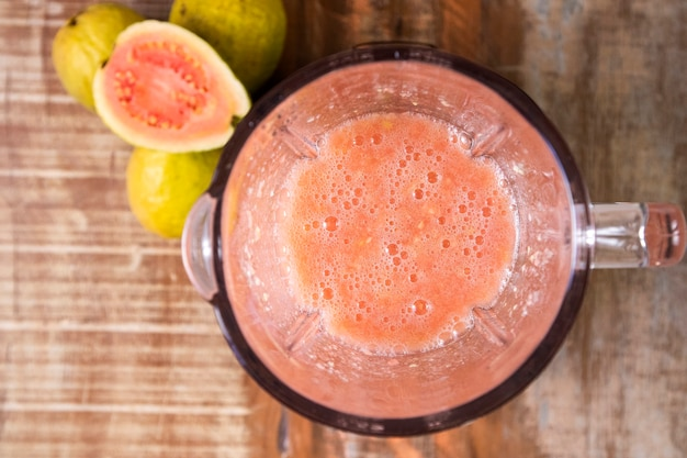 Red guava juice in a blender top view.