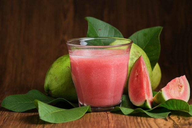 Red guava juice is served on a wooden background with guava fruit slices and leaf decorations