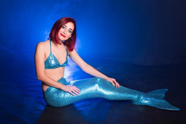 真っ青な海の水中で赤い髪の美しいサイレン人魚。