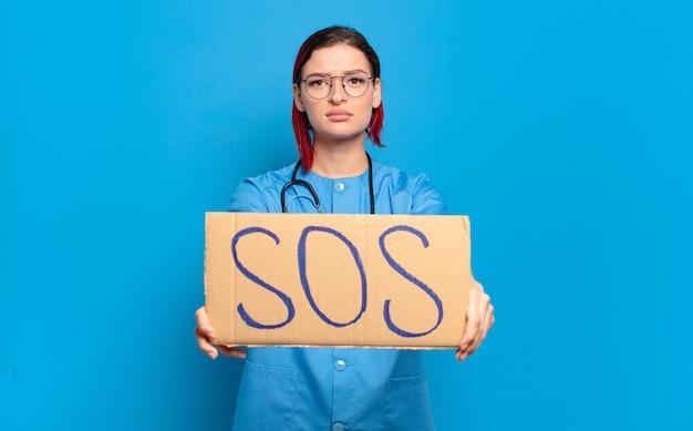 Sos 배너를 들고 빨간 머리 멋진 간호사